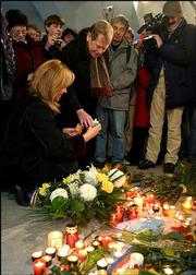 Former Czech president and dissident Vaclav Havel, right, accompanied by his wife, Dagmar, left, place a candle at the 1989 Velvet Revolution Memorial place at Narodni Trida in Prague, Czech Republic.