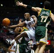 New Jersey's Jacque Vaughn drives to the basket between Seattle's Vladimir Radmanovic (77) and Rashard Lewis, rear. The Sonics defeated the Nets, 79-68, Wednesday night in East Rutherford, N.J.