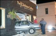 Lawrence Police officers investigate a one-car wreck at 14th and Massachusetts streets. Police say Kansas University student Martin J. Donaghy led them on a chase after leaving The Bottleneck early Thursday and eventually crashed his car into J. Gladman Gallery, 1401 Mass.