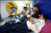 Kansas University freshmen Liz Mukherjee, foreground, from Overland Park, Kristen Wehkamp, center, Garden City, and Liz's twin sister, Katie Mukherjee, camp for seats at tonight's KU-Vermont basketball game in sleeping bags outside the men's locker room. The group has been in line at Allen Fieldhouse since 6 a.m. Monday.