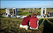 Texas A&M University students Caitlin Callaham, left, of El Paso, and her boyfriend, Jason Potthoff, of San Antonio, sit near the Bonfire Memorial in College Station, Texas, after the memorial's dedication. The granite and bronze memorial stands in the grassy field where a bonfire collapse five years ago claimed 12 lives and injured 27 people.