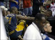 Indiana's Ron Artest scuffles with a fan after heading into the stands during the final minute of the Pacers-Pistons game. Officials ended the contest with 45.9 seconds left because of the brawl. The Pacers won, 97-82, Friday night in Auburn Hills, Mich.