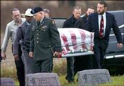 Chaplain Lt. Col. Larry Parrish leads pallbearers carrying the coffin of Sgt.1st Class Clinton Lee Wisdom at the Walnut Grove cemetery near St. Joseph, Mo. Wisdom was buried Thursday.