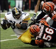 Pittsburgh Steelers running back Jerome Bettis (36) falls forward for extra yardage as he's tackled by Cincinnati defenders Brian Simmons (56) and Landon Johnson (59) in the second half. Bettis rushed for 129 yards in the Steelers' 19-14 victory Sunday in Cincinnati.