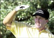 Phil Mickelson shades his eyes as his watches his tee shot on the third hole. Mickelson shot a 59 Wednesday in Poipu Beach, Hawaii, to win the Grand Slam of Golf.