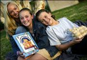 "Lori Mackey, left, founder of ""Prosperity 4 Kids,"" poses with her children Briana, 11, center, and Devin, 9, outside their home in Agoura Hills, Calif. Mackey, who was discouraged by the lack of resources available to teach her children about money, came up with a piggy bank system and a book ""Money Mama & the Three Little Pigs."""