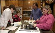 The Gauch family, from left, Brian, 13, David, 10, John and Susan, prepares for dinner at their Lawrence home. Not pictured is daughter Laura, 16. John and Susan Gauch, who are engineering faculty at Kansas University, would benefit from the free or reduced tuition for spouses and dependents of faculty and staff. The Gauches prepared dinner on Tuesday.