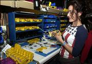 Taser International Inc. employee Lucy Lazarova assembles a law enforcement version of the popular stun gun. She worked on the guns last week at the company's headquarters in Scottsdale, Ariz. The company's stock has soared, but there are growing concerns whether the stun guns are as nonlethal as advertised. Below, Steve Tuttle, director of communications for Taser International, holds the X26c stun gun.