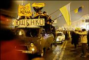 Opposition candidate Viktor Yushchenko's supporters ride atop a minibus in downtown Kiev, Ukraine. The signs read: Yushchenko, Lviv. Professors from the National University of Lviv were among the panelists Wednesday at a Kansas University forum discussing the country's disputed presidential election.
