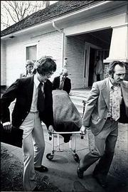 "The body of Shirley Vian is carried from her house in Wichita in 1977. Vian&squot;s death was one of the BTK serial killings that terrorized the city in the 1970s. The suspect goes by the name BTK, which stands for ""bind, torture, kill."" Authorities said earlier Thursday they were testing the DNA of a man arrested Wednesday on minor trespassing and housing code violations, state police said, but Wichita authorities denied the arrest was related to BTK."