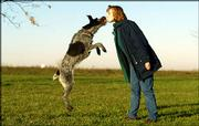 Six-year-old German wire-haired pointer, Providence, kisses her owner, Penny Shaffer, at Heritage Park in Olathe. The dog survived mouth cancer and a series of surgeries during the past week and will return to ringing the bell for Salvation Army this holiday season. She has rung the bell for the past four years.