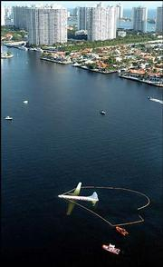 A Convair cargo plane is seen ditched in Maule Lake, surrounded by condominium towers in a densely populated Miami-Dade County neighborhood in Aventura, Fla. Pilot Alejandro Bristol and co-pilot Dennis Villavicencio were unhurt.