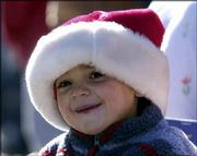 Benjamin Miller, 2, watches horse-drawn buggies and wagons go down Massachusetts Street in Saturday's Old-Fashioned Christmas Parade.