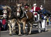 Santa Claus parades down Massachusetts Street in a horse-drawn carriage under the reins of Rob Phillips, who helped organize the Old-Fashioned Christmas Parade. Thousands lined Lawrence's downtown for a look at the 11th annual yuletide celebration.