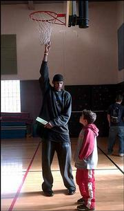 """Kansas University freshman basketball player C.J. Giles, left, towers over his """"little buddy,"""" fourth-grader Grant Ahlvers, during a visit to New York School. KU students in Life Skills for Student Athletes were reminded Tuesday to be good examples because children look up to them."""