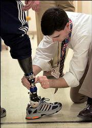 Andrew Steele, a prosthetist orthotist, makes an adjustment on the prosthetic leg of Army Stf. Sgt Ryan Kelly of Abilene, Texas, in this Jan. 13 file photo. For every American soldier killed in Iraq, nine others have been wounded and survived -- the highest rate of any war in U.S. history.