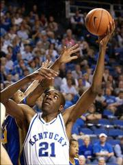 Kentucky's Shagari Alleyne lofts a hook shot over the defensive effort of Morehead State's Chad McKnight. The 10th-ranked Wildcats won, 71-40, Wednesday in Lexington, Ky.