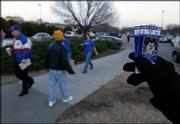 A ticket scalper advertises his merchandise on the Kansas University campus before last winter's KU-K-State game. Though legal in Kansas, scalping is not legal on university property.