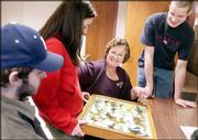 Joetta Weaver, third from left, who has spent 47 years working at Kansas University, views a display of mounted butterflies with students Adrian Zink, Larned, Kristen Kotarski, Fort Worth, Texas, and Joshua Carmichael, Hutchinson. The entomology department had a retirement party Monday for Weaver, who is leaving at the end of the month.
