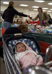 One-month-old Ayla Clark rests in a shopping cart as her mother, Sarah Acock, upper left, shops for gifts at the Toy Shop at the Douglas County Fairgrounds. The Toy Shop distributed gifts and clothing to families Monday at the fairgrounds. The annual event is co-sponsored by the Salvation Army and Toys for Tots.
