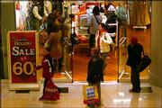 Holiday shoppers walk past a holiday sale display in the Manhattan Mall in New York. With less than two weeks left until Christmas, the nation's stores stepped up discounts during the weekend.