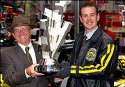 Car owner Jack Roush helps driver Kurt Busch, right, hoist the 2004 Nextel Cup trophy in New York's Times Square.