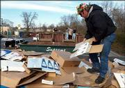 Charlie Brice flattens cardboard boxes in a recycling bin. The city of Springfield is encouraging that additional trash generated during the holidays be recycled.