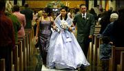Kenia Esparza, 15, center, walks arm-in-arm with her mother, Lucia, and father, Leonardo, following the Mass for Kenia's Quinceanera on Dec. 4 at the Sacred Heart Cathedral in Salina.