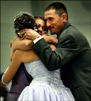 Kenia Esparza, 15, left, a Salina Central High School freshman, hugs her mother, Lucia, and her father, Leonardo, after giving her mother 15 roses at the 4-H Building in Salina. Each rose represents a year in Kenia's life and were presented to thank her mother as part of Kenia's Quinceanera ceremony. The ceremony is a rite of passage for Hispanic girls, similar to a debutante's coming out party.