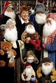 Jane Howard, of Kansas City, Mo., poses with her Santas of all sizes at a store in Weston, Mo. This is the first year that Howard's Santa creations, which are made in her home, are available to the public.