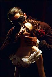 "The Phantom (Gerard Butler) embraces Christine (Emmy Rossum) in the musical drama ""Andrew Lloyd Webber&squot;s The Phantom of the Opera."""