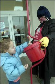 Samantha Angell, 4, Tonganoxie, drops some change in the Salvation Army kettle outside Sears, 2727 Iowa. Bundled up for the cold weather at right is bell ringer Martha Sower, Eudora. The Salvation Army's holiday collection campaign will end at 4 p.m. Friday. Wednesday, only about half of the 19 Salvation Army kettles in Lawrence were out because there weren't enough people to work the stations.
