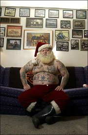 "Lawrence resident Chris Hartman portrays Santa Claus around town as a way to experience the ""Christmas magic."" Hartman, not your everyday Santa, displays his tattoos in his home."