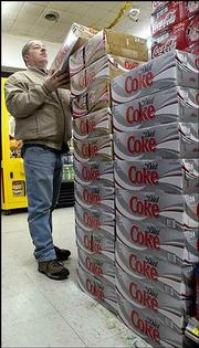 Marty Sutton, of Jonesville, Ind., selects a case of caffeine free Diet Coke at a store in Walesboro, Ind. Soda makers are offering more diet brands as consumers increasingly pick diet soda over regular soda.
