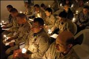 U.S. troops sing during a candlelight Christmas service at Forward Operating Base Marez in Mosul, Iraq. They were attending a midnight service.