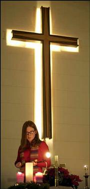 Hannah Newson, Lee's Summit, Mo., lights candles. The church, 609 E. 550 Road, was abuzz with activity as families gathered to celebrate.<br>