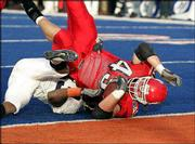 Fresno state's Stephen Spach rolls into the end zone over Virginia cornerback Tony Franklin in overtime. The referees ruled the play was a touchdown, and the Bulldogs won, 37-34, Monday at the MPC Bowl in Boise, Idaho.