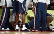 New Jersey's Vince Carter, the victim of cramps from dehydration, winces in pain during the Nets' 100-90 overtime loss to Detroit. Carter played his first game with the Nets on Monday in Auburn Hills, Mich.