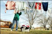 Helen Wonnell, who lives at 1633 E. 18th St., takes advantage of the warm weather Monday to hang her laundry outside. The warm trend is expected to last through the week.