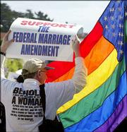 A supporter of the Federal Marriage Amendment is blocked by a gay American flag from a protester before a march from the Sts. Paul and Peter Church through North Beach in San Francisco in this April 3, 2004, file photo. Though gay-marriage opponents made headway in the November elections, a constitutional ban on the issue will face many obstacles in Washington.