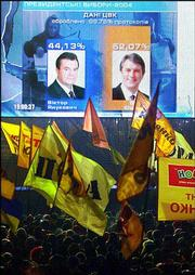 Supporters of opposition leader Viktor Yushchenko watch a TV news broadcast with the preliminary presidential election results on a giant screen during a rally Monday at the Independence Square in Kiev, Ukraine. With ballots counted from 99.84 percent of precincts, official results gave Yushchenko 52 percent of the votes compared with 44 percent for Kremlin-backed Prime Minister Viktor Yanukovych.