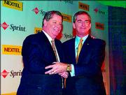 Tim Donahue, left, president and CEO of Nextel Communications, and Gary Forsee, chairman and CEO of Sprint Corp., shake hands after their Dec. 15 announcement that the companies intend to merge -- and move corporate headquarters to Virginia.