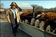Richard Ice, who was named 2004 Outstanding 4-H Alumni, feeds his cattle. Ice started building a herd after buying his first bucket calf as a 4-H project.