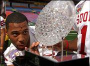 Oklahoma defensive back Eric Bassey studies the national-championship trophy during a break in Sunday's media day. The winner of tonight's Orange Bowl in Miami takes the hardware home.