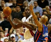 Miami's Shaquille O'Neal, left, looks to pass against New York's Stephon Marbury. O'Neal had 33 points and 18 rebounds as the Heat beat the Knicks, 102-94, Wednesday night in Miami.