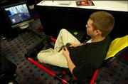 Justin Campbell demonstrates the Hot Seat at the Consumer Electronics Show. The gaming chassis features surround sound and vibration for an arcade-like experience in the home.