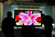 Workers at Samsung's booth at the Consumer Electronics Show adjust the world's largest plasma television, a 102-inch screen prototype, at the Las Vegas Convention Center. The annual trade show occupies 1.5 million square feet of exhibit space and attracts 120,000 attendees.