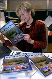 Sally Lunsford, spokeswoman for the Kansas Department of Commerce, looks over items featuring the state's new advertising campaign and slogan. The material was released during a news conference Friday in Topeka.
