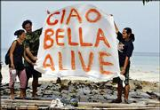 Isari Chanswan, left, her boyfriend, Umberto Giovi, 42, from Rio Elba, Italy, center, and Anucha Jangho, a restaurant staffer, hold a banner they made to signal rescue flights after the tsunami destroyed their restaurant on the island of Phi Phi, Thailand. Giovi and the staff of Ciao Bella restaurant fled to the hills for 12 days before returning to the beach Friday to find what was left of their restaurant.