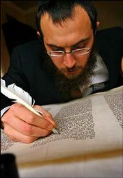 Rabbi Mendel Lifshitz works to repair letters in an old Torah at his family's Boise, Idaho, home that doubles as Idaho's only Chabad center for classes, religious services and social gatherings. The Torah was rescued in Europe during World War II.